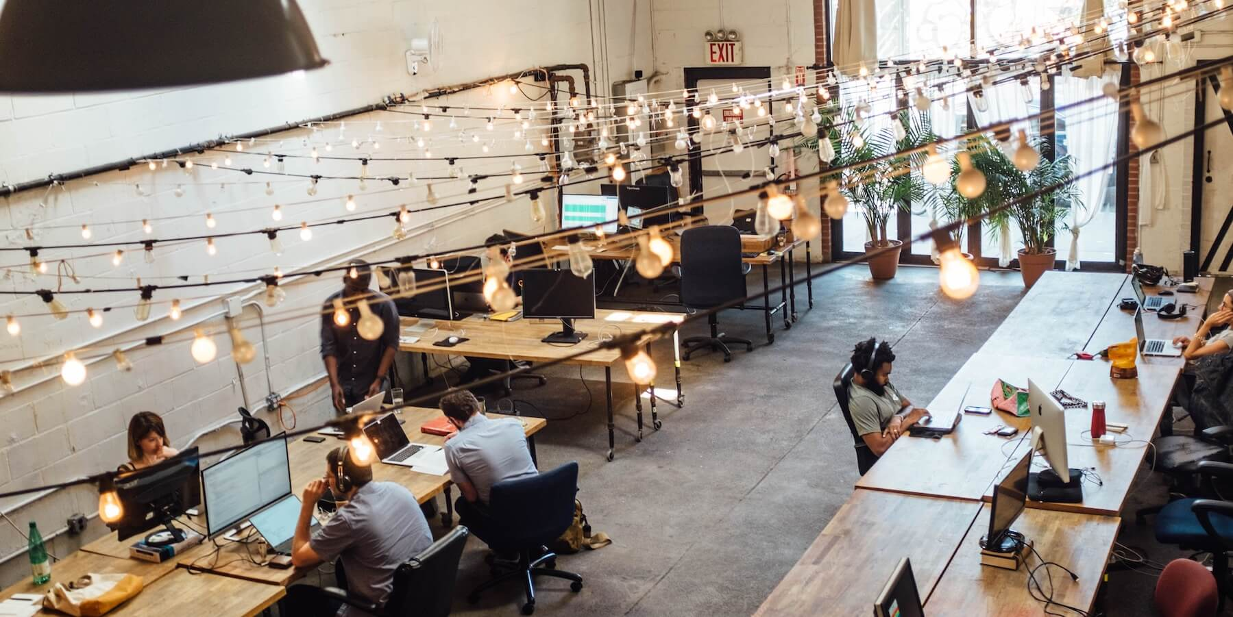 People working under string lights in a bright and airy coworking space